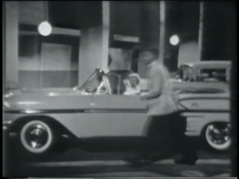 B/W 1958 zoom in teen couple parking Chevrolet Impala convertible at prom / boy opens door for girl