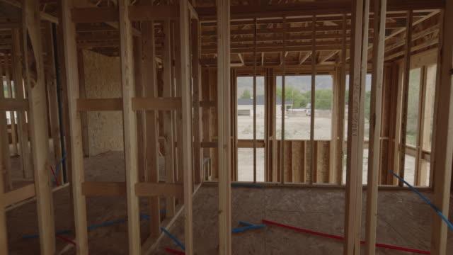 vídeos de stock e filmes b-roll de zoom in through framing of interior of house under construction / pleasant grove, utah, united states - proprietário de casa