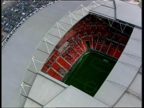 Zoom in through roof of Wembley Stadium to crowd seated inside London