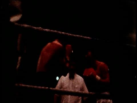 zoom in through ropes on blurred image of boxers fighting in ring uk - ボクシングリング点の映像素材/bロール