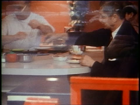 1958 zoom in thru window waiter serving hamburger to man at diner counter who puts ketchup on it - hamburger stock videos & royalty-free footage