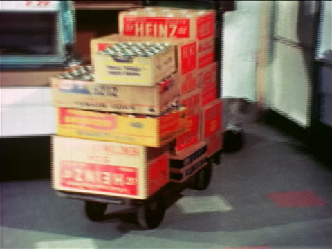 1965 zoom in tilt down pan male grocer pushing cart full of boxes of canned goods thru doorway in store - canned food stock videos & royalty-free footage