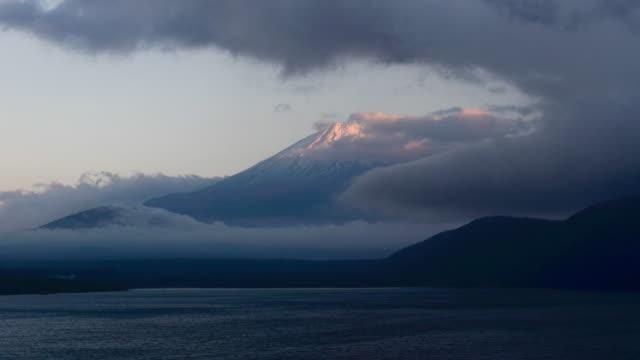 vídeos de stock, filmes e b-roll de 4k zoom fuji de montanha de lapso de tempo com pôr do sol e nuvem noite no lago motosu, prefeitura de yamanashi, região de chubu, japão - vídeo de estoque - desaparecer gradualmente