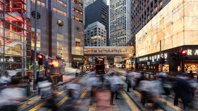 tl/zi/pd zoom in time lapse of hong kong's financial district, with business people and commuters crossing road at rush hour - organisation stock videos & royalty-free footage