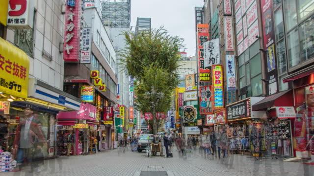 vídeos y material grabado en eventos de stock de 4k zoom in time lapse : shinjuku downtown area en tokio , japón - letrero de tienda