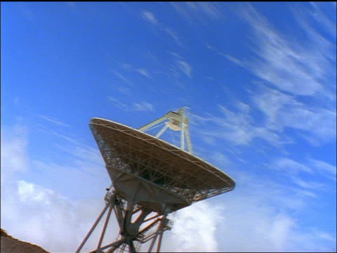 canted zoom in time lapse wispy clouds in blue sky over large satellite dish/radio telescope / hawaii - wispy stock videos & royalty-free footage