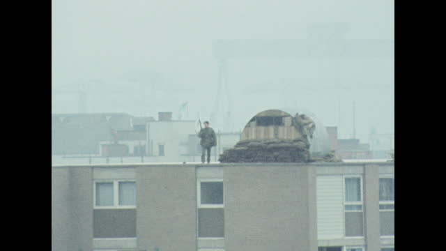 zoom in to a british soldier observing shankill road from rooftop, belfast; 1970. - zoom in stock videos & royalty-free footage