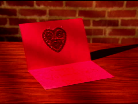 zoom in to a close-up of a homemade valentine card on a table. - card table stock videos & royalty-free footage