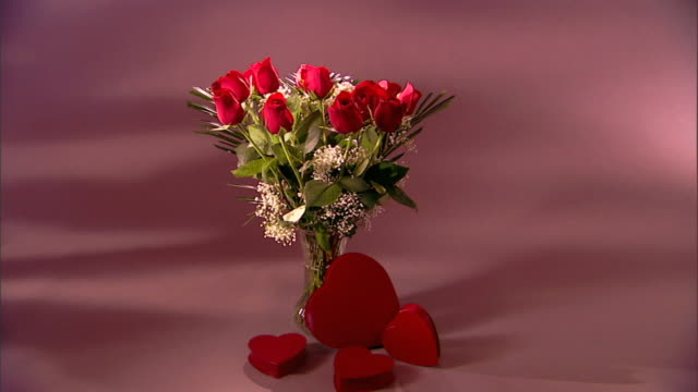 Zoom in to a medium shot of a bouquet of red roses with boxes of Valentine candy.