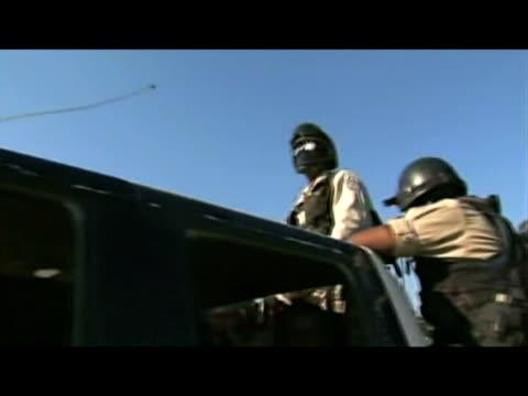vídeos de stock e filmes b-roll de zoom in to armed police officers sitting in patrol van following devastating earthquake haiti; 16 january 2010 - hispaniola