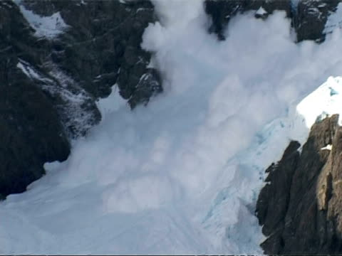 Zoom in to CU avalanche, snow falling down from glacier, Antarctica