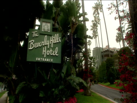 zoom in to beverly hills hotel entrance sign surrounded by lush gardens hotel in background hollywood - hollywood california stock videos & royalty-free footage