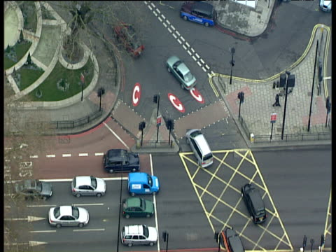 Zoom in to black taxi cabs driving over congestion charge road markings