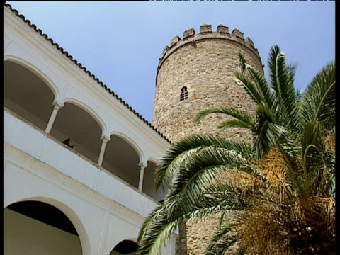 Zoom in to castle tower and white balconies with palm fronds in foreground Zafra