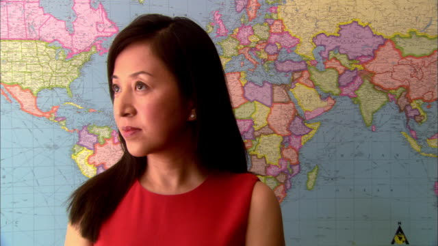 zoom in to close up asian woman standing in front of world map, turns to look at camera - world politics stock videos & royalty-free footage