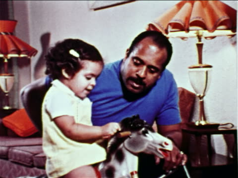 vídeos de stock e filmes b-roll de 1968 zoom in to close up black man talking to + kissing small girl on rocking horse indoors / educational - 1968