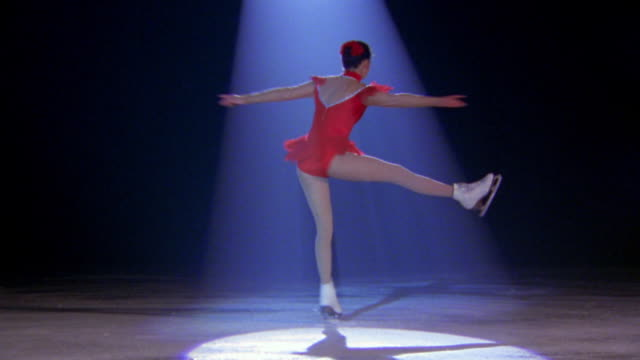 zoom in to close up female figure skater spinning posing with leg out then closing pose to spin faster / tilt down tilt up