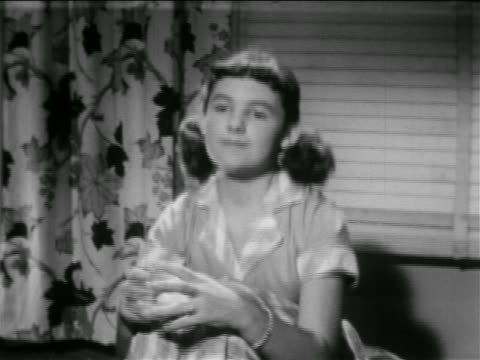 vídeos de stock, filmes e b-roll de b/w 1953 zoom in to close up girl in pigtails putting chin on hands on knees with thoughtful look / educational - preto e branco