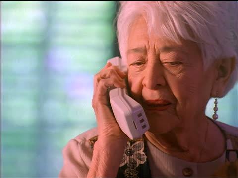 zoom in to close up hispanic senior woman talking on cordless telephone + laughing - sladdlös telefon bildbanksvideor och videomaterial från bakom kulisserna