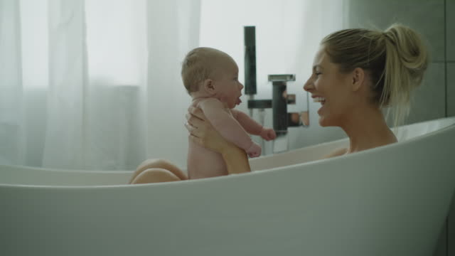 vídeos de stock e filmes b-roll de zoom in to close up of mother playing with baby son in bathtub / lehi, utah, united states - nu
