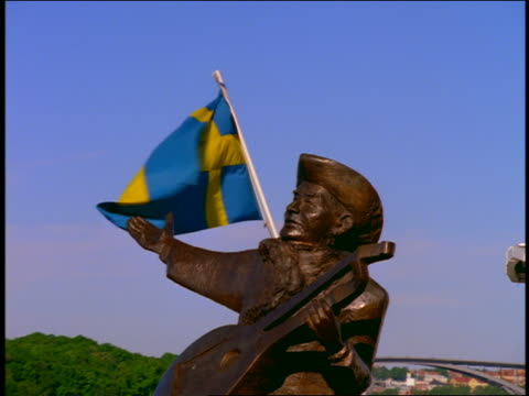 zoom in to close up of statue of musician with swedish flag blowing in background / riddarsholmen, stockholm, sweden - swedish flag stock videos and b-roll footage