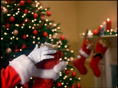 zoom in to close up Santa Claus' hand putting gift in stocking with fireplace + Christmas tree in background