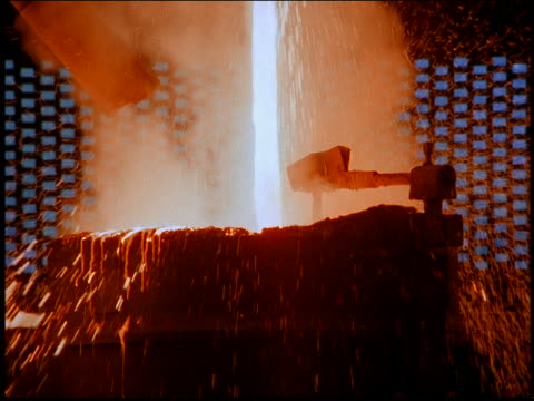 vídeos de stock, filmes e b-roll de zoom in to close up with tilt up of molten metal pouring into + spilling over large vat in steel mill / brazil - metarlúgica