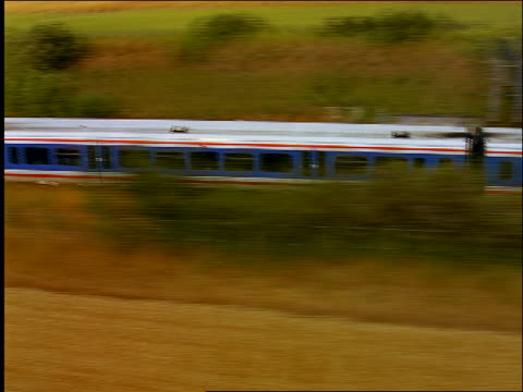 aerial zoom in to close up + zoom out of commuter train going through countryside / shottesbrooke, berkshire, england - berkshire england stock videos and b-roll footage