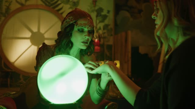 stockvideo's en b-roll-footage met zoom in to concerned fortune teller with crystal ball reading palm of customer in nightclub / provo, utah, united states - handpalm