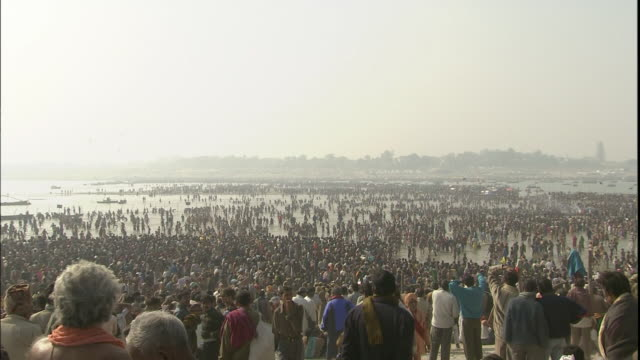 zoom in to crowds of kumbh mela pilgrims taking ablution in ganges, india - large stock videos & royalty-free footage