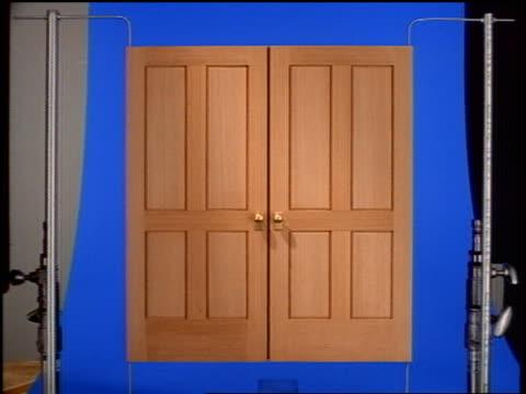 zoom in to doors opening to blue screen in studio - whatif点の映像素材/bロール