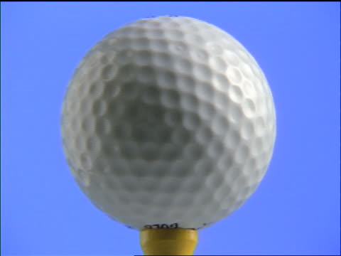 zoom in to extreme close up of golf ball spinning on tee with blue background / zoom out - golf ball stock videos & royalty-free footage
