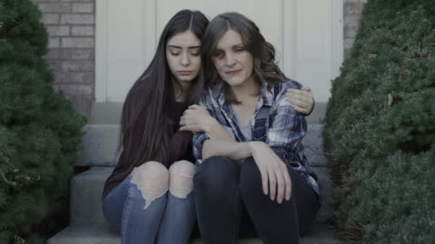 zoom in to girl comforting crying mother with black eye on front stoop / springville, utah, united states - arm around stock videos & royalty-free footage
