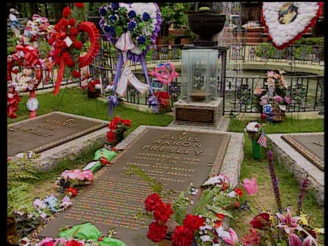 Zoom in to grave of Elvis Presley in between his parents' graves surrounded by wreaths