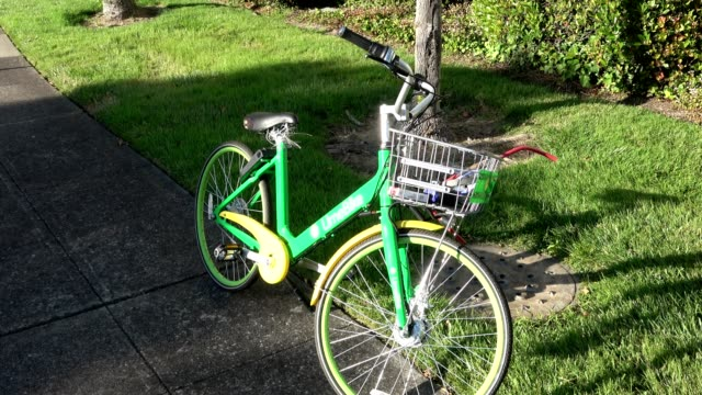 zoom in to logo on crossbar, high-angle view, of dockless rentable bicycle from startup lime parked on alameda island, alameda, california, june 11,... - zoom in点の映像素材/bロール