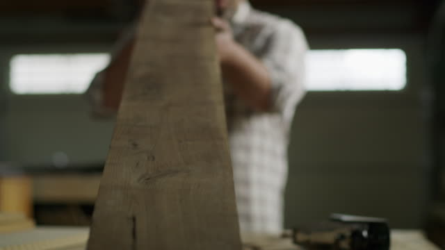 zoom in to man examining plank of wood in workshop / provo, utah, united states - provo video stock e b–roll