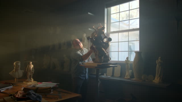 Zoom in to man in studio sculpting statue in natural light from window / American Fork, Utah, United States