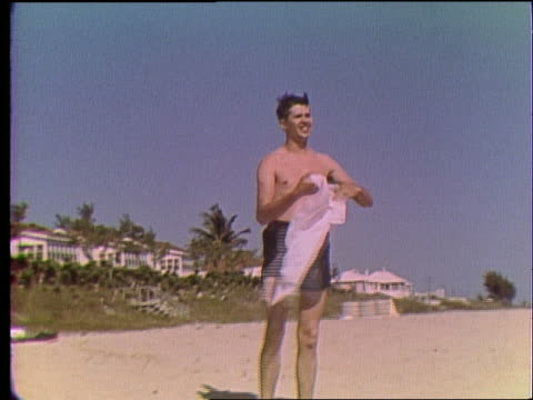 vidéos et rushes de zoom in to man in swimsuit drying off with towel on beach - serviette de bain