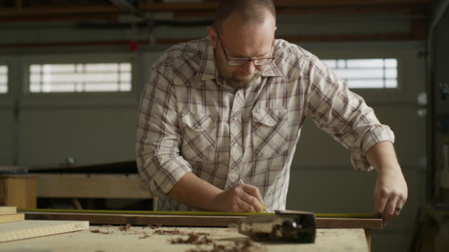 zoom in to man measuring wood with tape measure in workshop / provo, utah, united states - provo video stock e b–roll