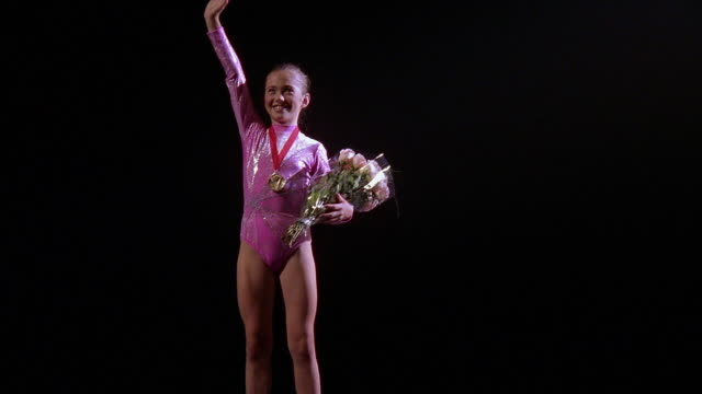 vidéos et rushes de zoom in to medium shot young female gymnast wearing medal, holding flowers, smiling and waving - médaille récompense