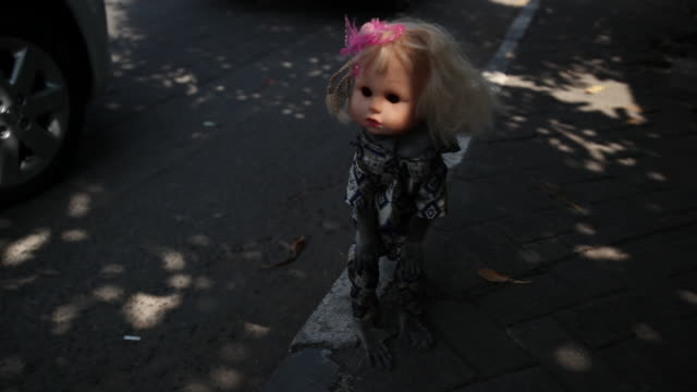 zoom in to monkey dressed as doll on streets of jakarta. - doll stock videos and b-roll footage