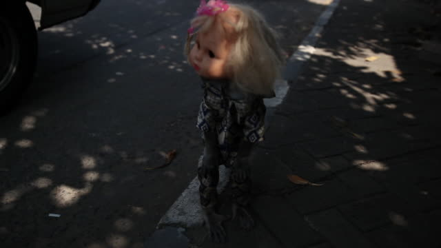 Zoom in to monkey dressed as doll on streets of Jakarta.