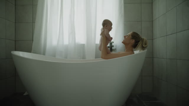 zoom in to mother playing with baby son in bathtub / lehi, utah, united states - vasca da bagno video stock e b–roll