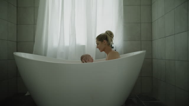zoom in to mother washing head of baby son in bathtub / lehi, utah, united states - tile stock videos & royalty-free footage