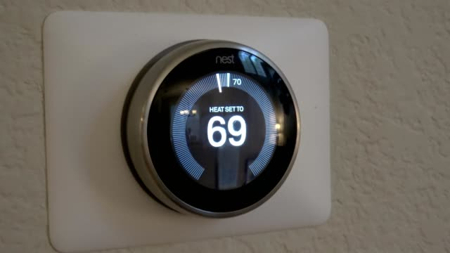 zoom in to nest learning thermostat mounted on the wall of a domestic living room, a smart home remote controlled thermostat from google inc, san... - remote control video stock e b–roll