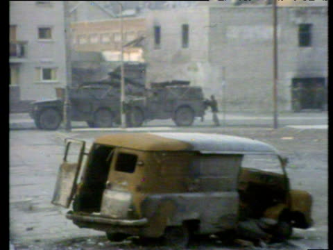zoom in to paratroopers running past armoured car pursuing rioters in bogside area bloody sunday londonderry; 30 jan 72 - nordirland stock-videos und b-roll-filmmaterial