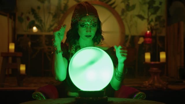 vidéos et rushes de zoom in to portrait of fortune teller waving hands over crystal ball in nightclub / provo, utah, united states - sphère