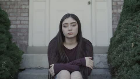 vídeos y material grabado en eventos de stock de zoom in to portrait of girl with attitude sitting on front stoop / springville, utah, united states - esfuerzos problemas