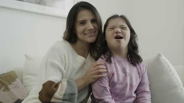 zoom in to portrait of proud mother sitting with daughter with down syndrome / lehi, utah, united states - disability stock videos & royalty-free footage
