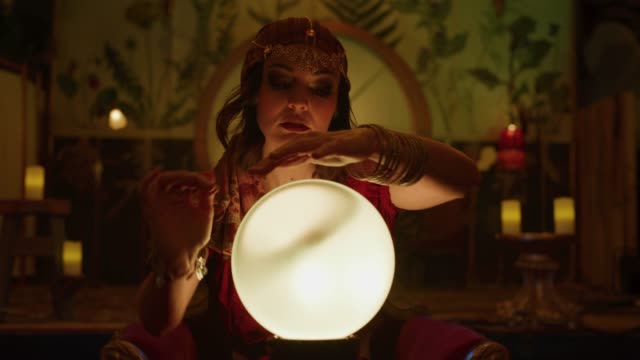 zoom in to portrait of smirking fortune teller with crystal ball in nightclub / provo, utah, united states - kostümierung stock-videos und b-roll-filmmaterial